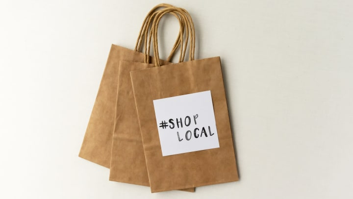 Paper bags with handle with #ShopLocal stamp.