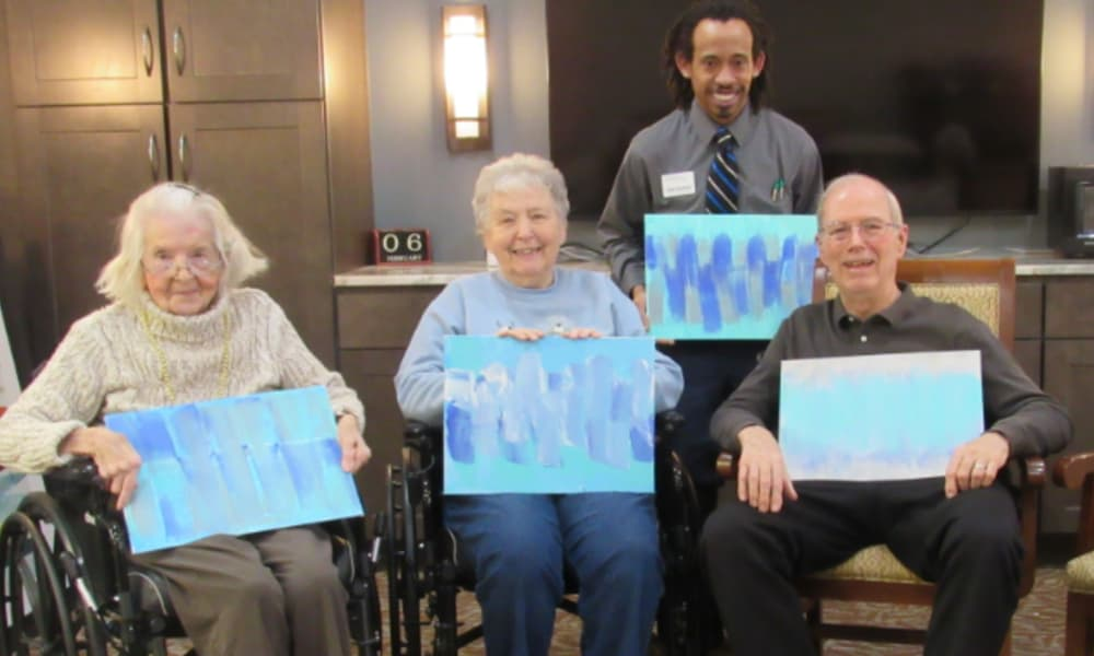 senior residents and staff displaying their paintings