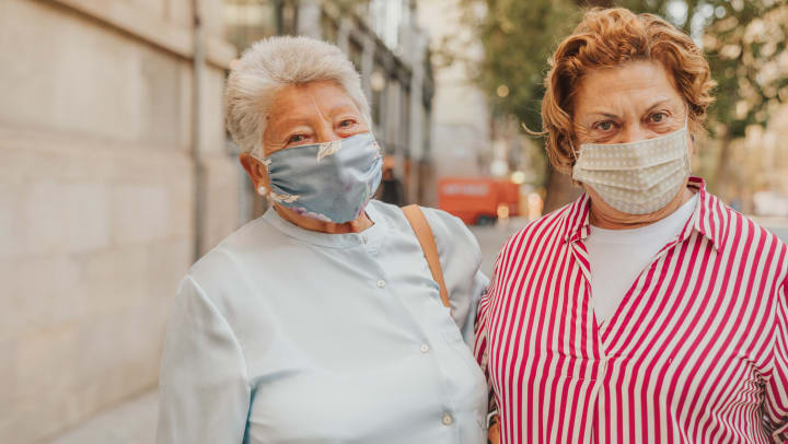 Two elderly women walking down the road with mask on looking at camers