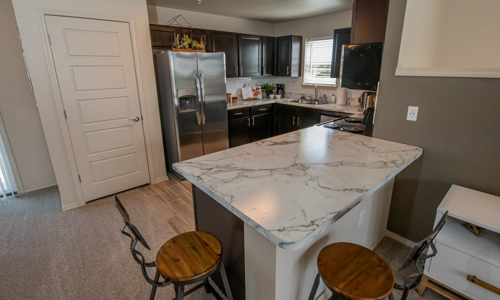 Loft kitchen with espresso cabinets and white countertops with pantry at Cottages at Crestview in Wichita, Kansas