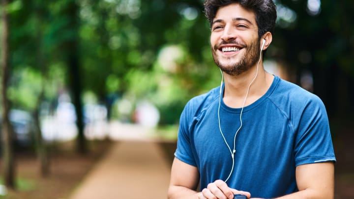 Man smiling in the park after running