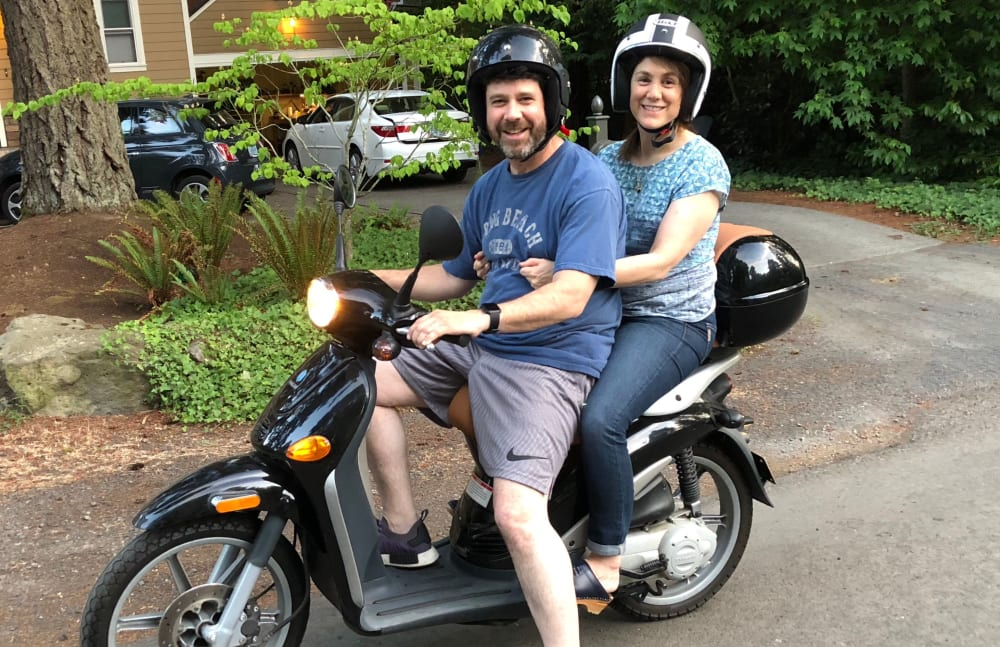 Joe from Touchmark Central Office in Beaverton, Oregon and his wife on a moped