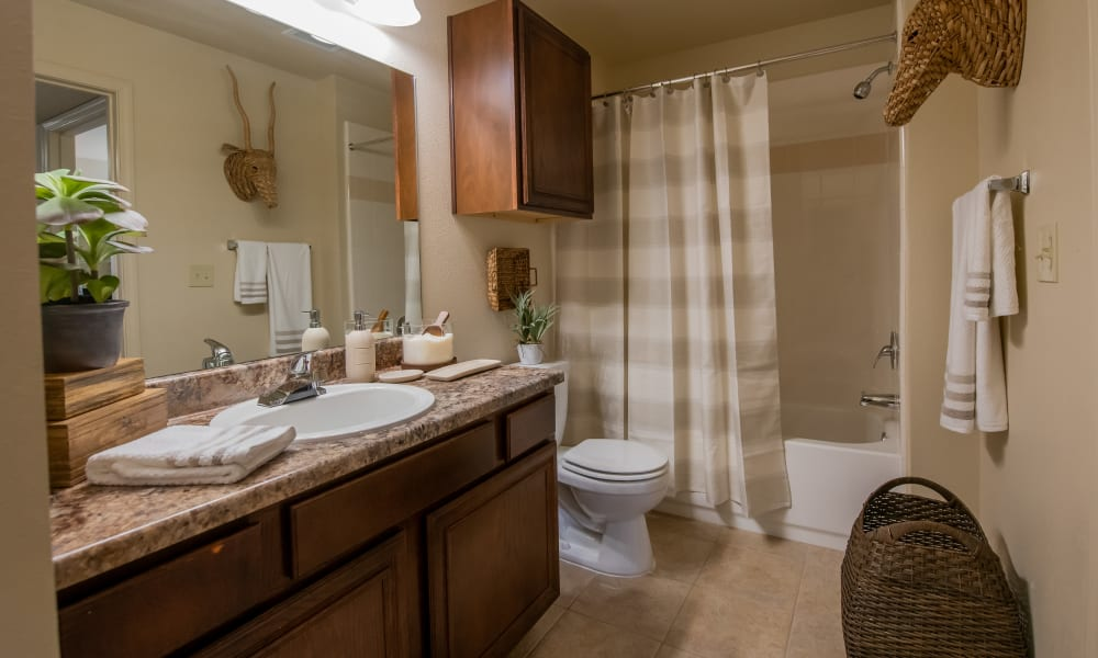 Fully equipped bathroom with tub and shower combo at Coffee Creek Apartments in Owasso, Oklahoma