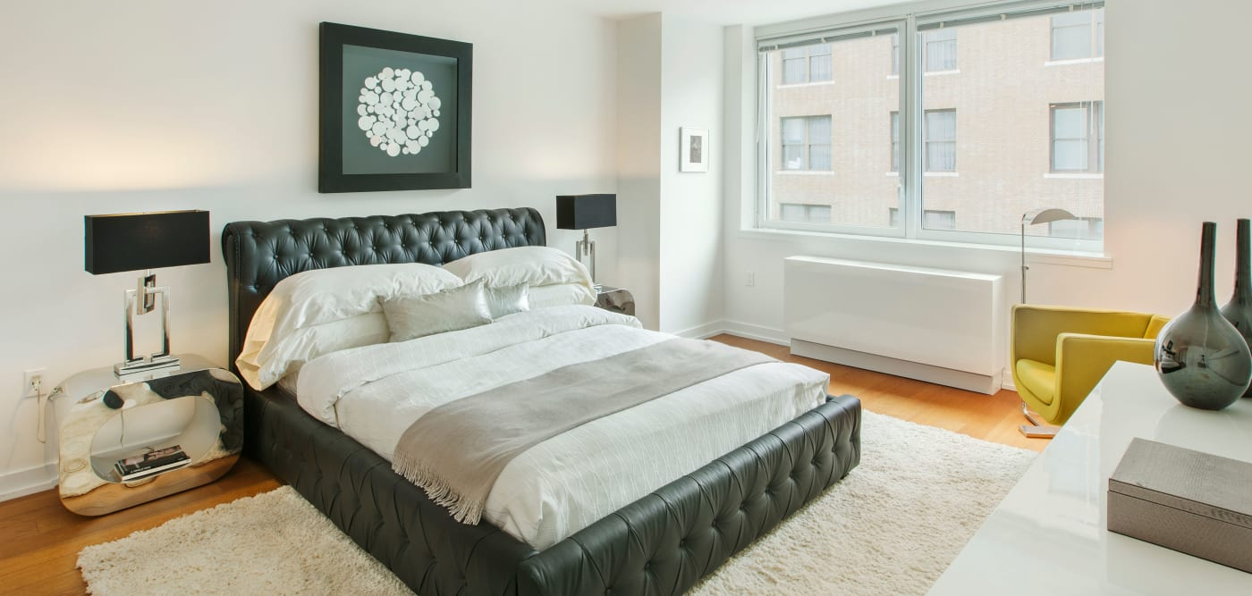 Master bedroom with large windows for natural lighting at The Larstrand in New York, New York