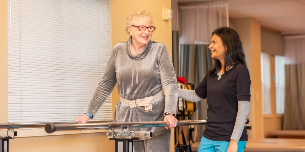 A staff member helping a resident with balance at Mission Healthcare at Bellevue in Bellevue, Washington.