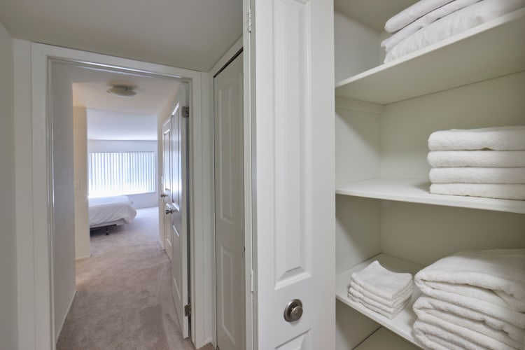 Linen shelf and a view of the bedroom at Sage Luxury Apartment Homes