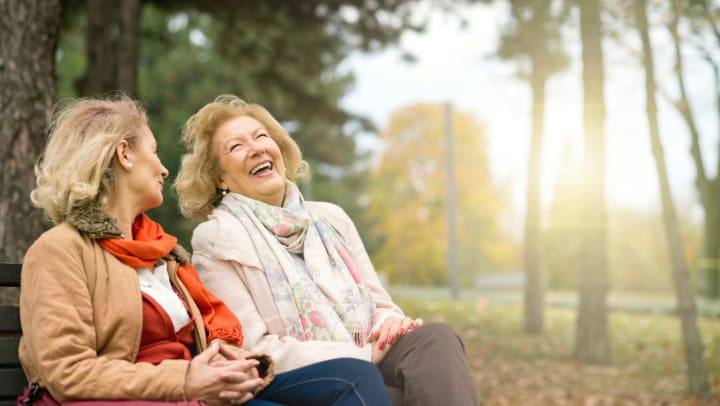 Two senior women sitting on a park bench laughing.