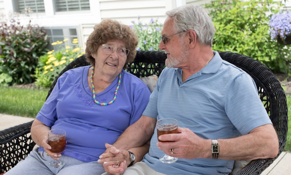 A resident couple enjoying some beverages outside at The Keystones of Cedar Rapids in Cedar Rapids, Iowa.