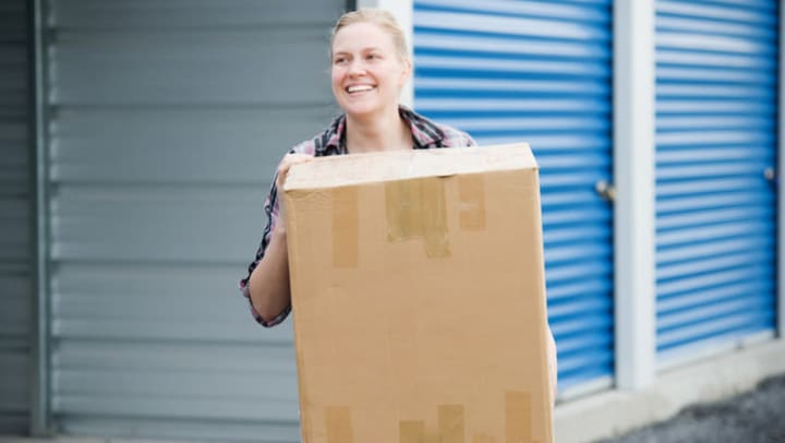 Woman at storage facility carrying a box