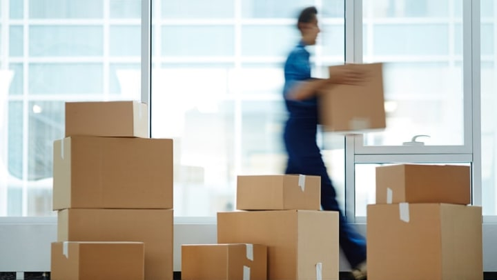 Blurred motion of worker carrying packed box to new office