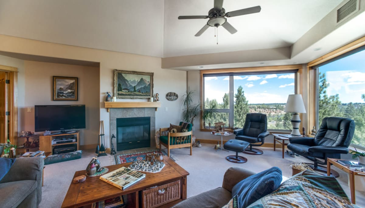 An apartment living room with large windows that overlook Bend at Touchmark at Mount Bachelor Village in Bend, Oregon
