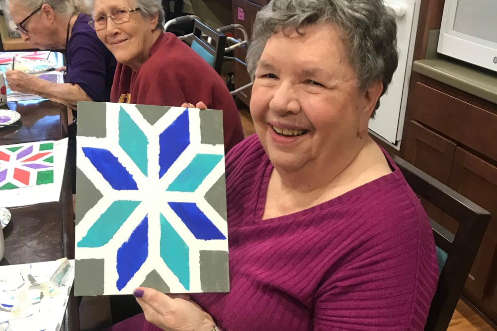 Resident holding up a piece of art at Edencrest at The Legacy in Norwalk, Iowa