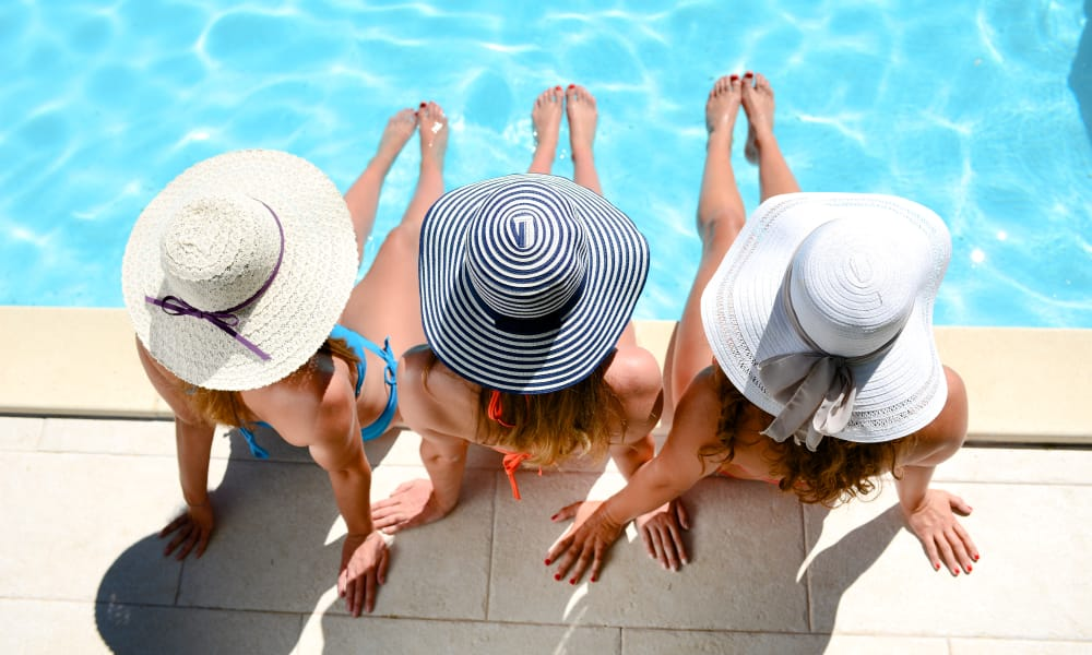 Three ladies with sun hats by the pool at Seventeen15