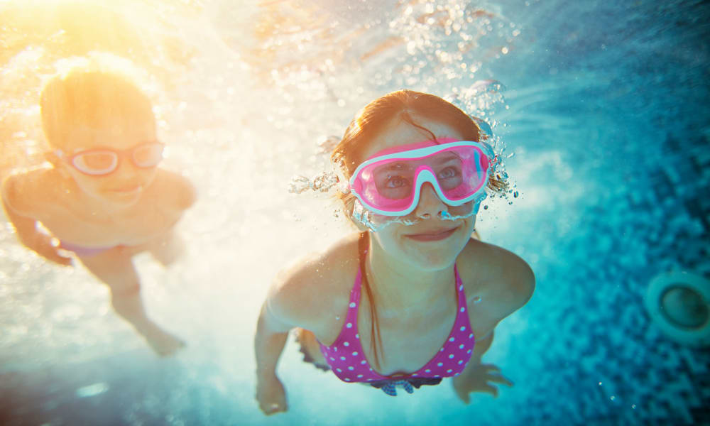 Kids exploring the pool with goggles on at Bonterra Apartments in Fort Wayne, Indiana