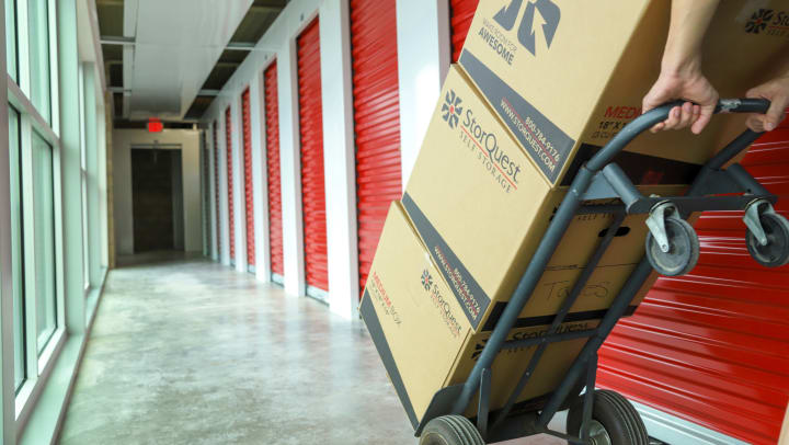 A person rolling a hand cart with three storage boxes stacked on it down a hallway
