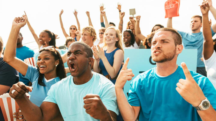 A group of people wearing shades of blue standing and cheering at a sporting event