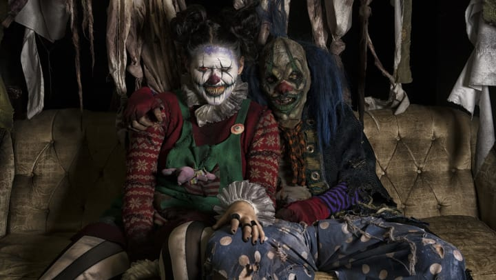 Two very scary clowns sitting on a rugged couch at Reindeer Manor near Olympus at Ross