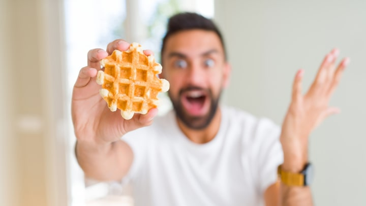 Young man with a surprised face holding a small Belgian waffle