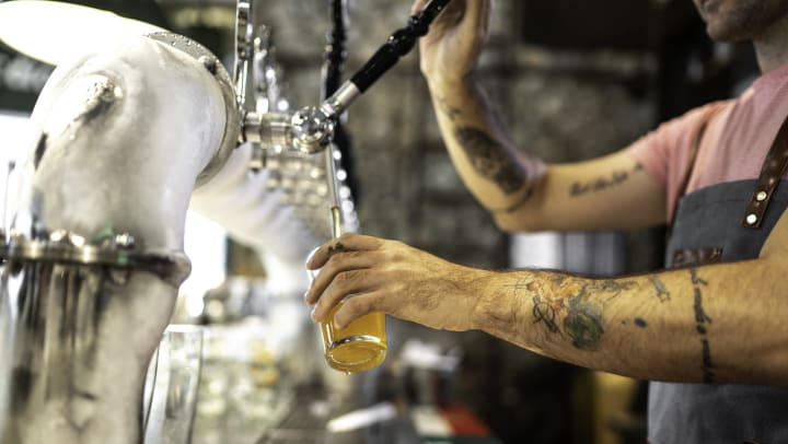 Bartender with tattooed arms pouring beer from a tap