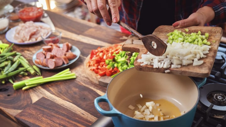 Person holding a cutting board and pushing chopped onions and celery into a Dutch oven on a stovetop. Sliced sausage, chicken, okra, and red bell peppers can be seen in the background.
