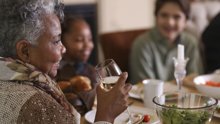 A senior woman sits with family to enjoy a holiday dinner.