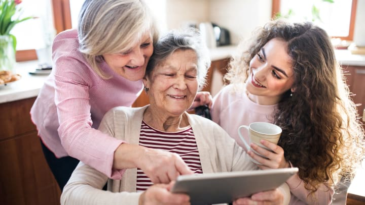 A middle-aged woman, elderly woman, and young woman look at a tablet together.