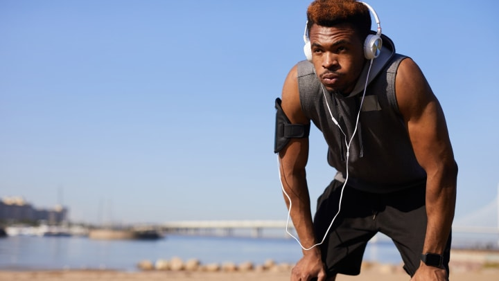 Man resting from hard workout with headphones on and hands on his knees