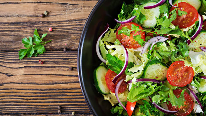 A bowl of fresh greens salad with tomatoes, red onions, and cucumber, seen from above