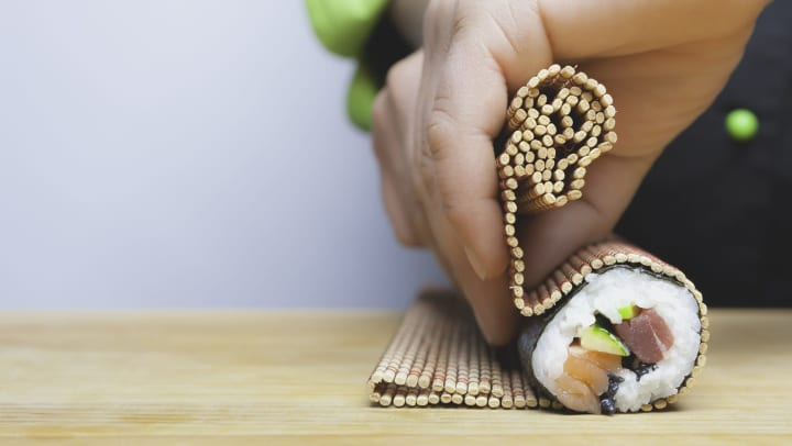 Person rolling sushi on a wood cutting board.