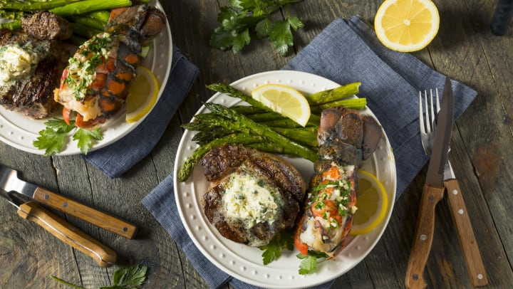 Lobster, steak, and asparagus on a plate with utensils and lemon wedge set on a wood table.
