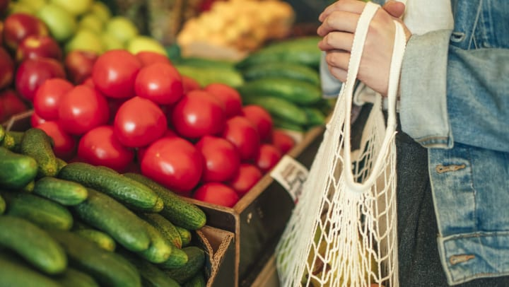 A customer stands in front of a fresh produce stand at a farmers market, holding a reusable mesh bag.