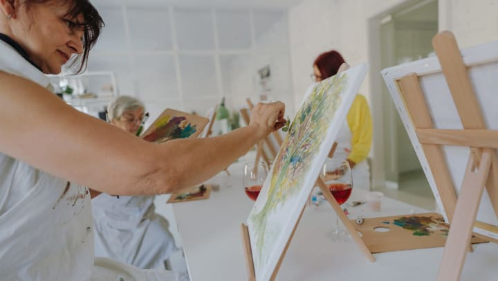 Women painting on canvases in a white room with glasses of wine.