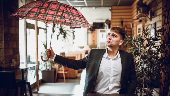 Man holding an open umbrella inside a restaurant and looking at it with a frown.