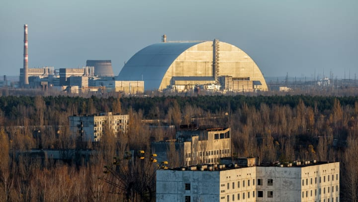 A long-distance shot of the Chernobyl power plant in the background and the Ukrainian city of Pripyat in the foreground.