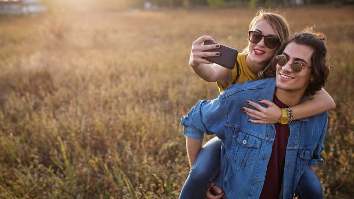 A young man piggybacks his girlfriend in a field while she takes a selfie