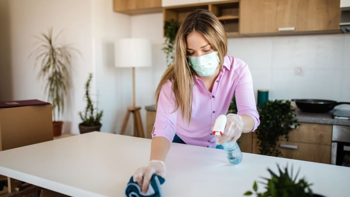 Woman in face mask spraying and scrubbing a kitchen countertop.