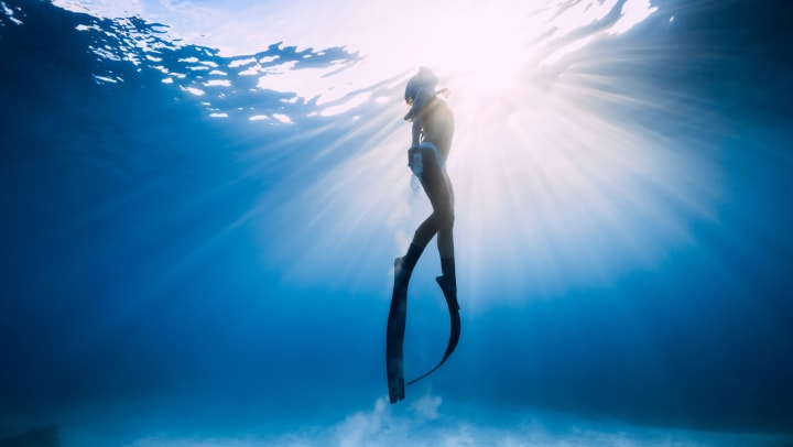 Woman swimming in the ocean with scuba gear