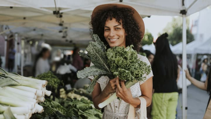 A smiling woman in a summer dress is buying kale at a farmers market.