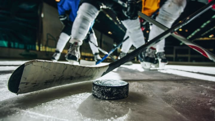Close-up of a hockey stick about to strike a puck. Hockey players are seen in the background.