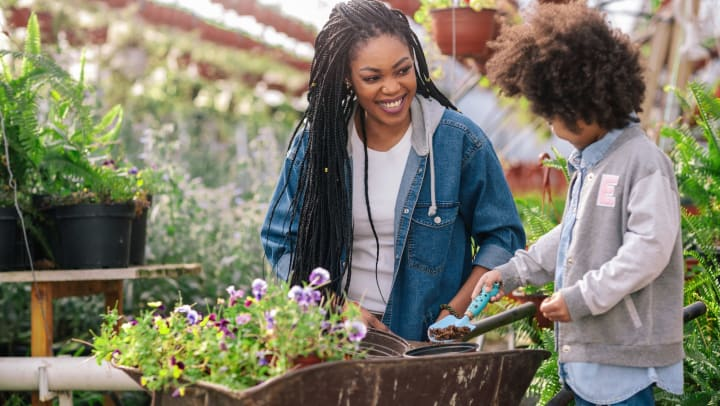 Mother and daughter smiling while picking out plants at a garden center.