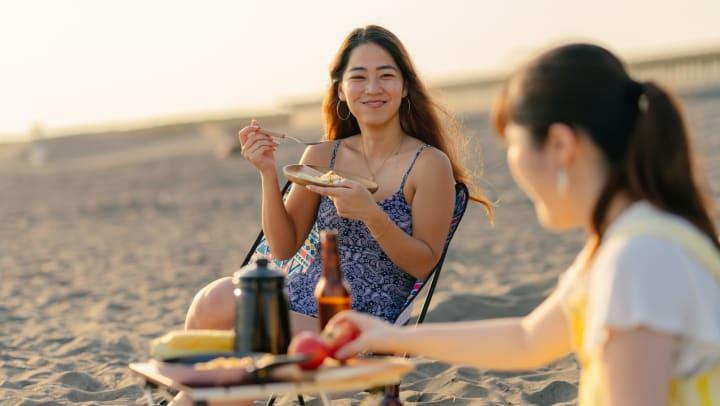 Two women sitting on the beach, enjoying a picnic.