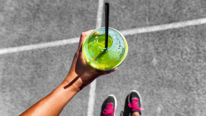 An overhead view of a woman standing on concrete in running shoes while holding a cup of bright green juice.
