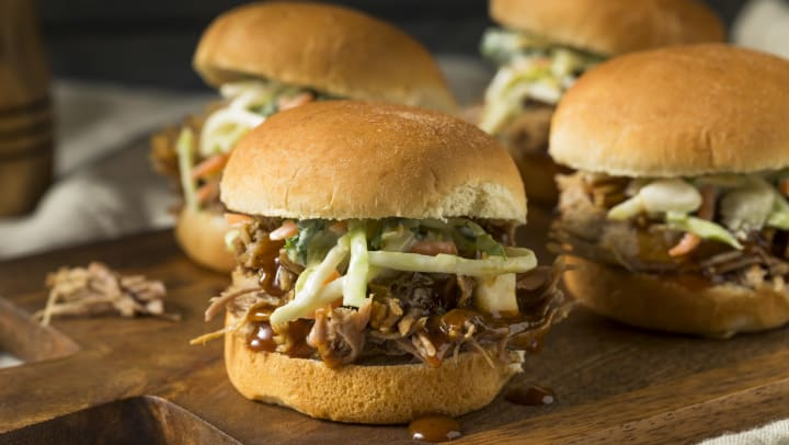 Four gourmet pulled pork sliders with slaw and sauce on a wood cutting board.