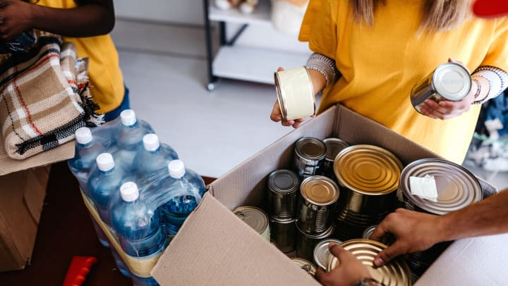 Three people pack boxes full of canned food