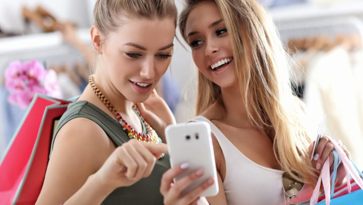 Two women in a store looking at a smartphone