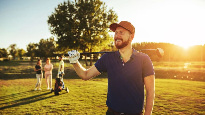 A man smiling while holding a golf club on a backlit golf course in the afternoon.