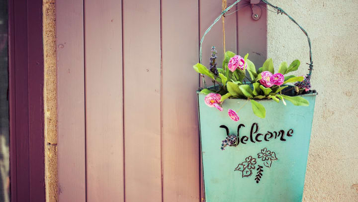 """A basket hung on a purple door that reads """"Welcome"""" and holds pink flowers."""