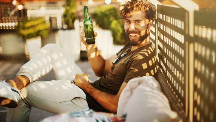 Man sitting outdoors, leaning against lattice, with a beer in his hand, smiling at the camera.