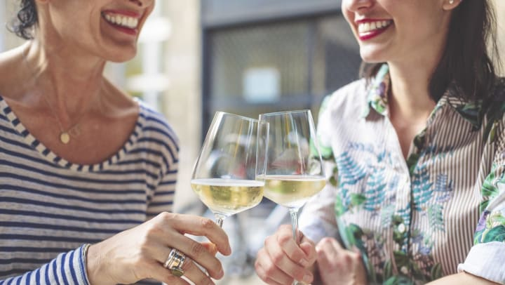 Two smiling women seated at an outdoor table holding glasses of white wine