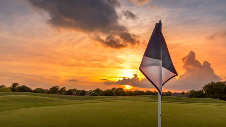 Golf flag with a golf course and orange sky in the background